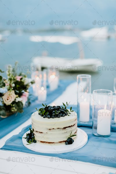 cake with blueberry and blackberry with candles lit around outdoors