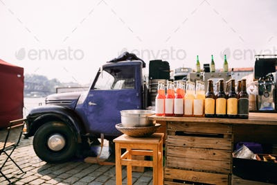 Lemonade, Cider And Other Drinks In Bottles Are Exhibited On A Wooden Counter Near Truck With Food