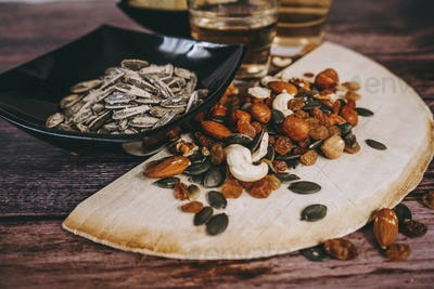 Mix of snacks with chips, nuts, seeds and beer