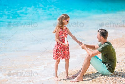 Young dad applying sun cream to daughter nose on the beach. Sun protection