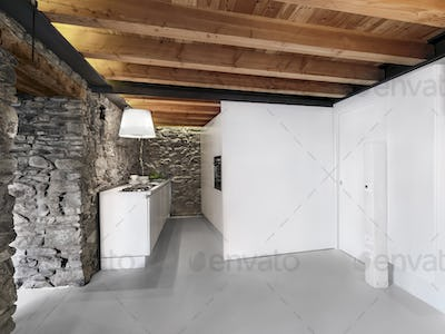 Interiors of a Modern Kitchen with Stone Wall and Wooden Beamed Ceiling