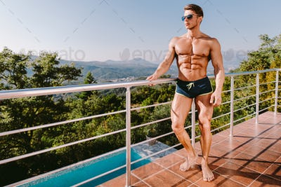 Fashion Portrait Of A Muscular Man In swim trunks At Swimming Pool