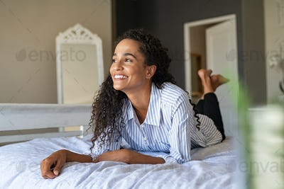 Happy young mixed race woman relaxing on bed