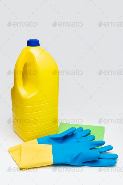 Bleach bottle, protective gloves and rag