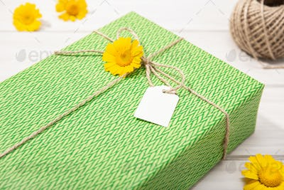 Green Gift or present box with blank label and daisy flowers on table
