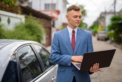 Young businessman with laptop in the streets outdoors