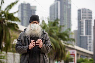 Mature bearded hipster man with mask using phone outdoors