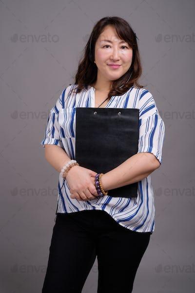 Portrait of mature Asian businesswoman holding clipboard