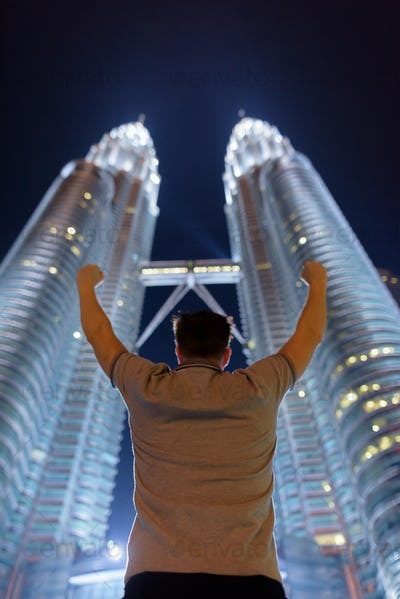 Young handsome man against view of the Petronas Twin Towers at n