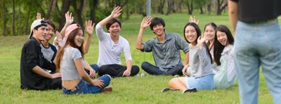 Happy young group of friends greeting together at the park