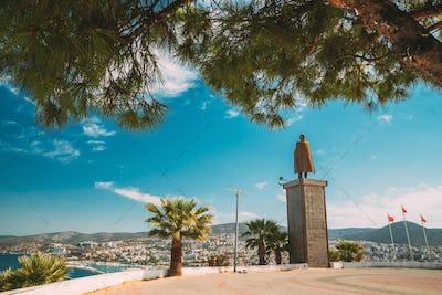 Kusadasi, Aydin Province, Turkey. Ataturk monument And Kusadasi Cityscape In Sunny Summer Day