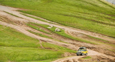 Yellow SUV Car On Off Road In Spring Hilly Landscape. Drive And Travel Concept