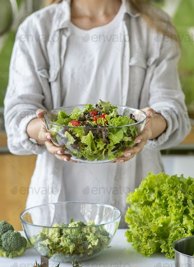 Unrecognizable woman making fresh salad in the kitchen