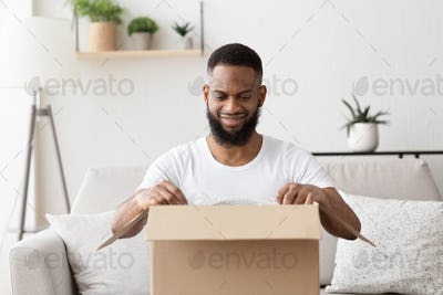 Glad african american millennial guy opens big box