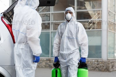 Man in coronavirus suit holding spray bottles with disinfecting chemicals