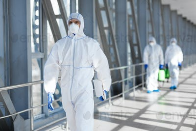 Virologists wearing protective hazmat suits making researches