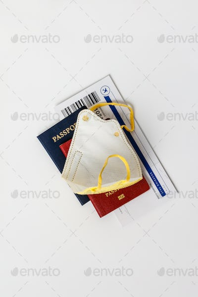 Coronavirus and travel concept. Passports, airplane tickets and medical mask flat lay.
