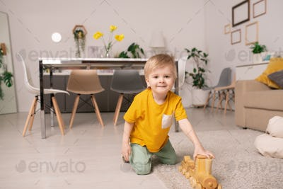 Happy cute little boy playing with wooden train while sitting on the floor