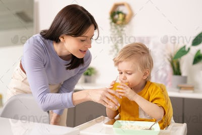 Young woman holding glass of juice by mouth of her cute little son drinking it