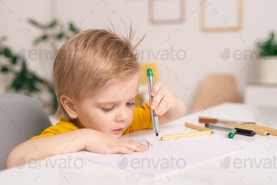 Cute little boy with green crayon or highlighter over paper drawing picture
