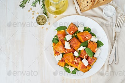 Salad with roasted pumpkin, feta cheese, spinach, nuts with honey and seasonings, top view