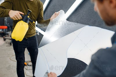 Workers wets car protection film before applying