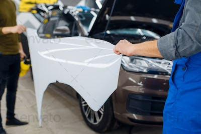 Male workers holds template of car protection film