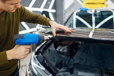 Male worker dries car protection film on hood