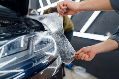 Worker applies car protection film on front fender