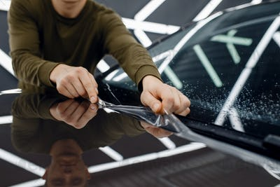 Worker installs protection film on car hood