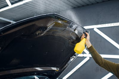 Male worker wets car hood surface with spray