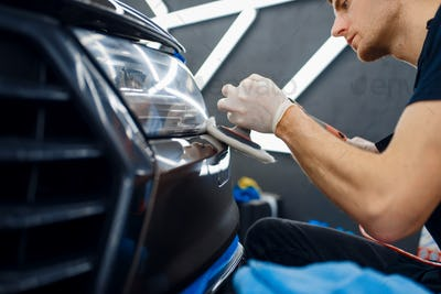 Male worker polishes front bumper, car detailing