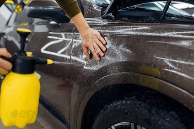 Male worker wets car fender surface, detailing