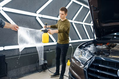 Male workers wets template of car protection film
