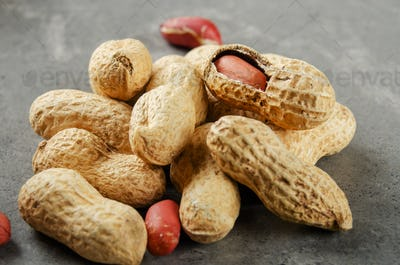 Ripe organic Peanuts in shell on stone table. Healthy eating concept