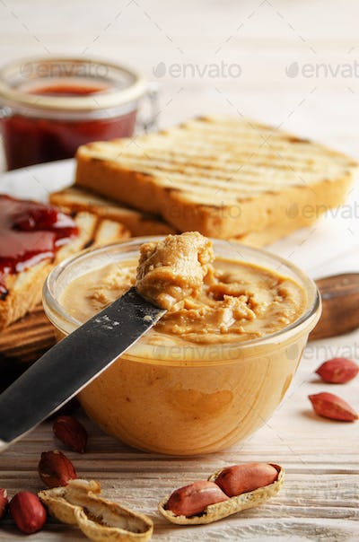 Low angle view at glass bowl with peanut butter on white wooden table with toasts and jam aside