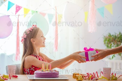 Caucasian girl is dreamily smiling. Festive colorful background with balloons. Birthday party and