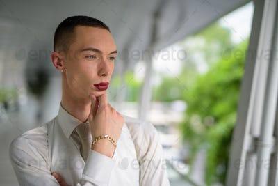 Young androgynous homosexual LGTB man thinking outdoors