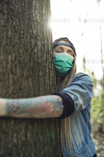 Casual Woman Hugging Tree in Park Wearing Face Protection Mask Against Coronavirus
