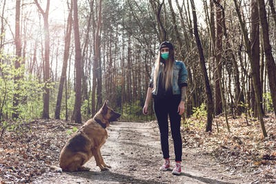 Woman Play with Dog Outdoor  Wearing Face Mask. Coronavirus New Normal.