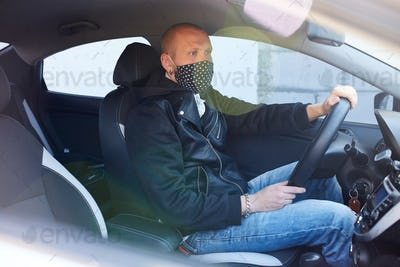Man with protective mask adriving a car by Coronavirus pandemic quarantine