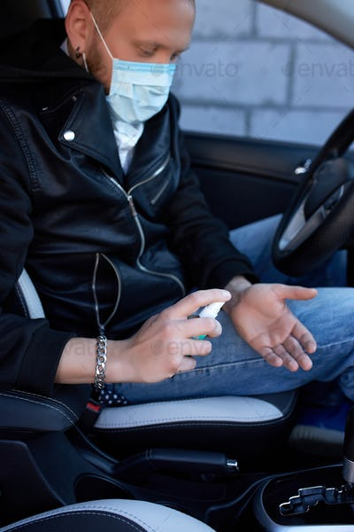 Man in protection mask sitting in the car, spraying hands antibacterial sanitizer spray
