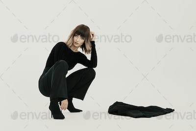 Portrait young woman sitting with attitude on white background