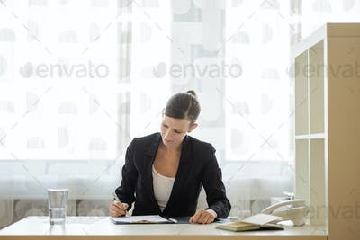 Young businesswoman or lawyer signing document