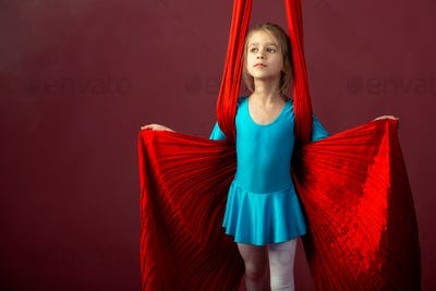 Charming little girl in a blue gymnastic suit