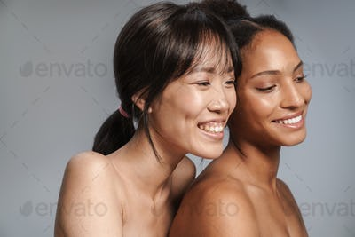 Portrait of two multinational half-naked women hugging and laughing