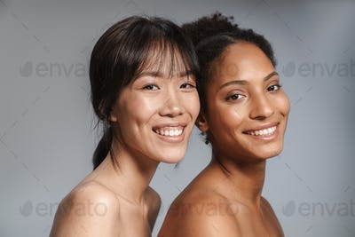 Portrait of two multinational women posing together and smiling