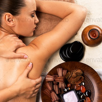 Young healthy woman relaxing and getting back massag.