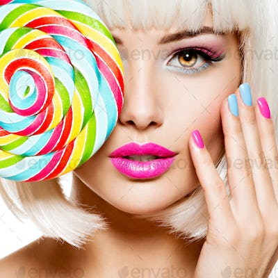 Face of a beautiful  girl with pink eye make-up and multicolor nails. Sweet candy.