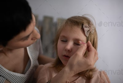 Mother helping daughter to apply makeup